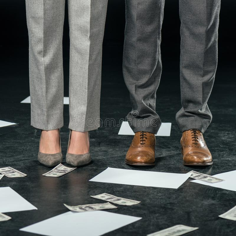 Low section view of businesspeople standing on floor with documents and money,. On black royalty free stock photos