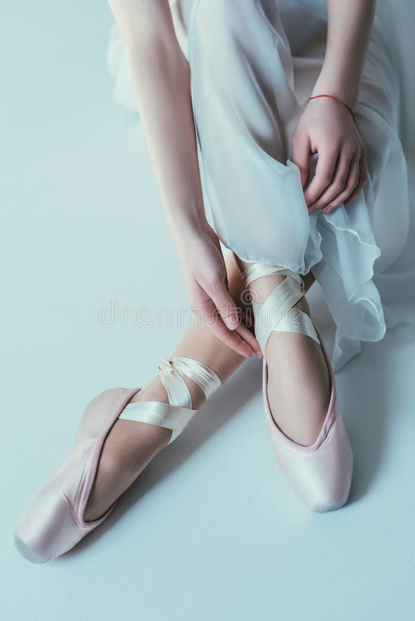 Low section view of elegant ballerina in white dress. And ballet shoes royalty free stock images