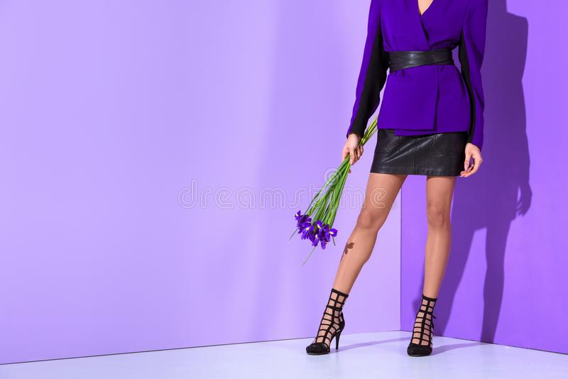 Low section view of elegant mulatto girl. Posing in purple jacket with irises at ultra violet wall royalty free stock photos