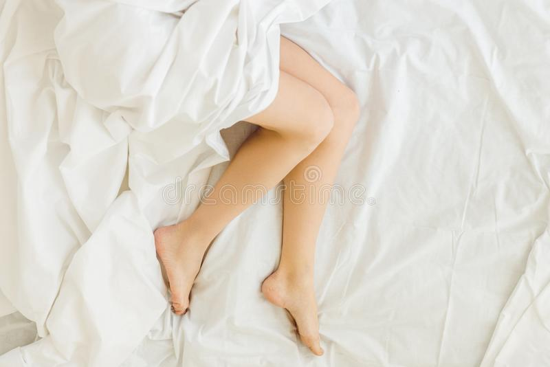 Low section view of female legs in bed. At home royalty free stock photography
