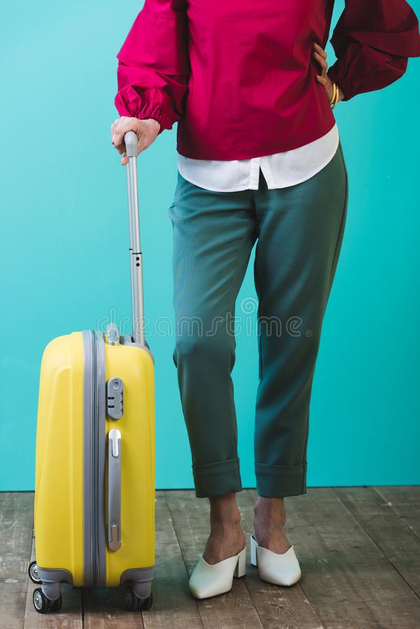 Low section view of female traveler. With yellow suitcase royalty free stock photo