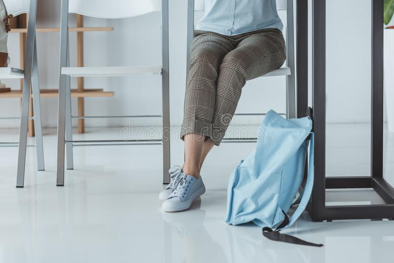 Low section view of girl sitting at table with backpack. On floor royalty free stock images