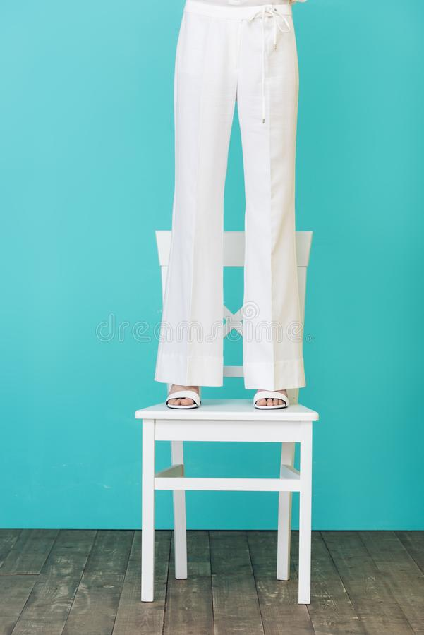 Low section view of girl in stylish white outfit standing on chair. On blue royalty free stock photo