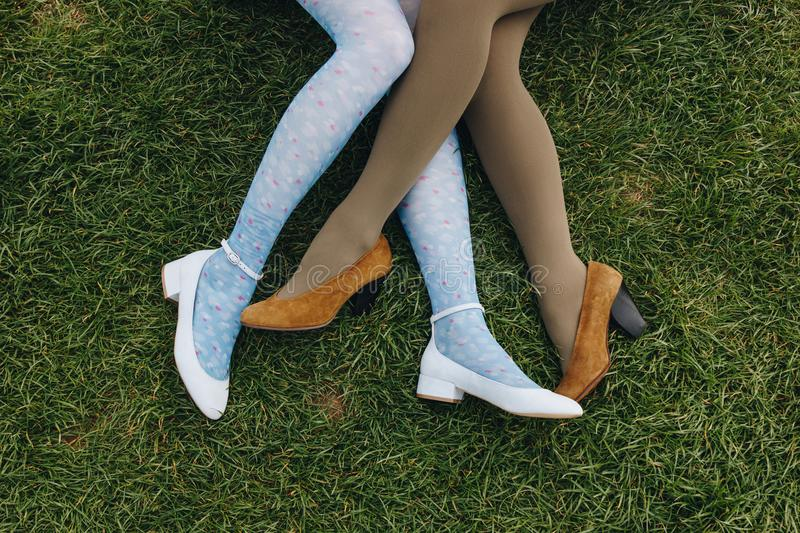 Low section view of girls in trendy shoes lying on green grass, Etretat,. Normandy, France royalty free stock image