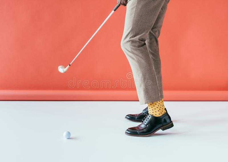 Low section view of golfer with golf club and ball,. On red stock image