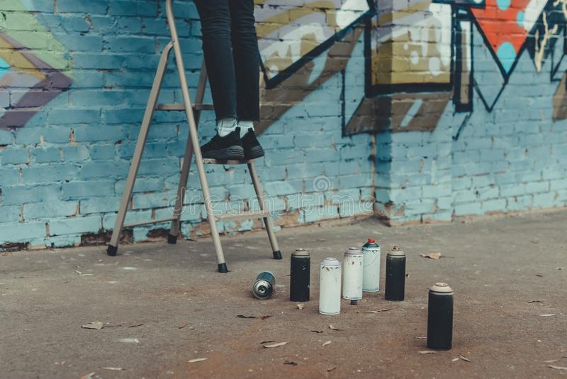Low section view of man. Painting colorful graffiti, spray paint on foreground royalty free stock photography
