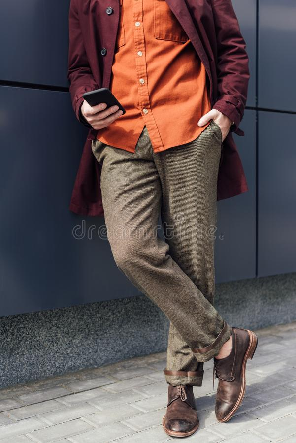Low section view of man. In trendy clothes using cellphone royalty free stock image