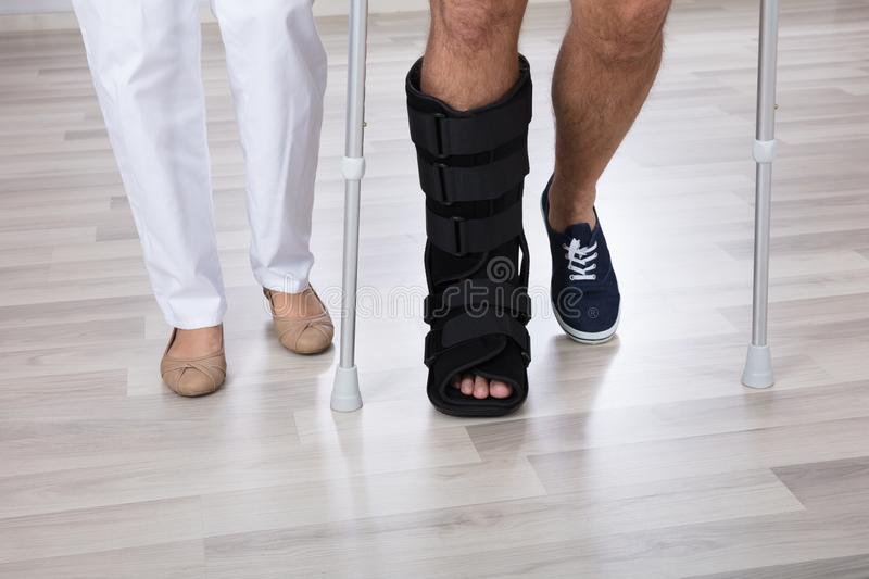 Low Section View Of Physiotherapist And Injured Person`s Leg. Wearing Walking Brace stock photo