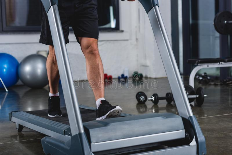 Low section view of sportsman. In sneakers jogging on treadmill in gym stock image