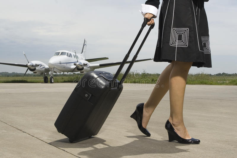 Low section view of a woman pulling her luggage at an airport. With a private jet in the background royalty free stock photos