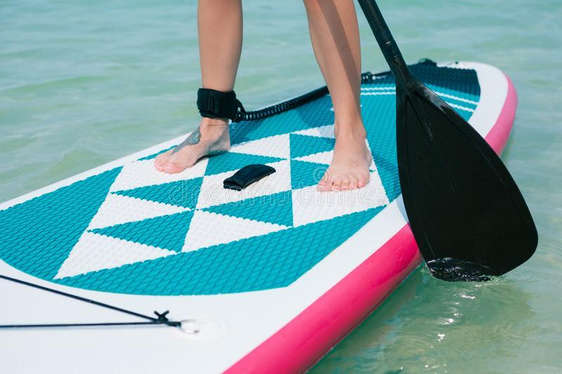Low section view of woman. On stand up paddle board on sea at tropical resort stock images