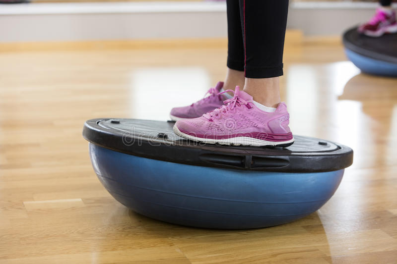 Low Section Of Woman Exercising On Bosu Ball. In health club royalty free stock image