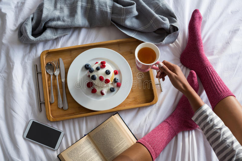 Low section of woman having breakfast on bed royalty free stock images