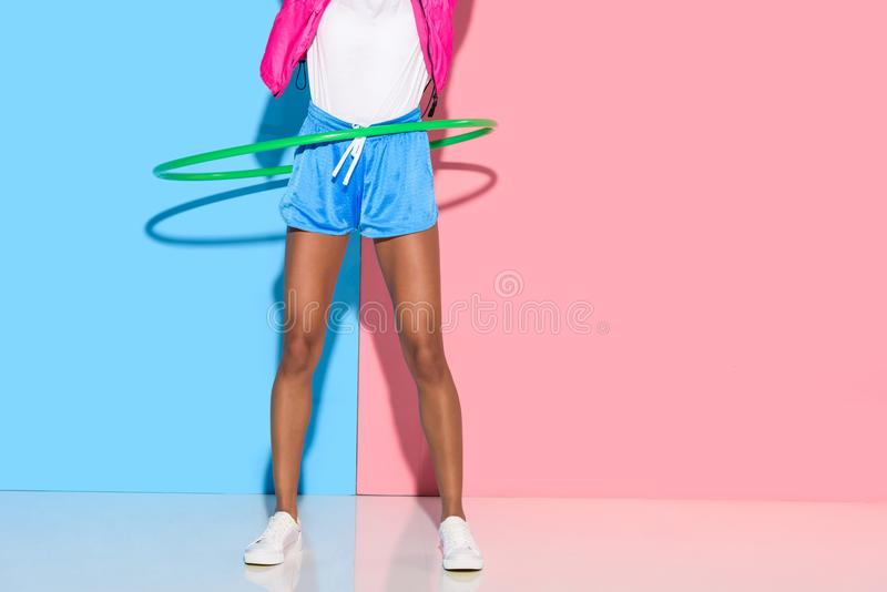 Low section of woman posing while exersizing with hoop on pink and blue background stock image