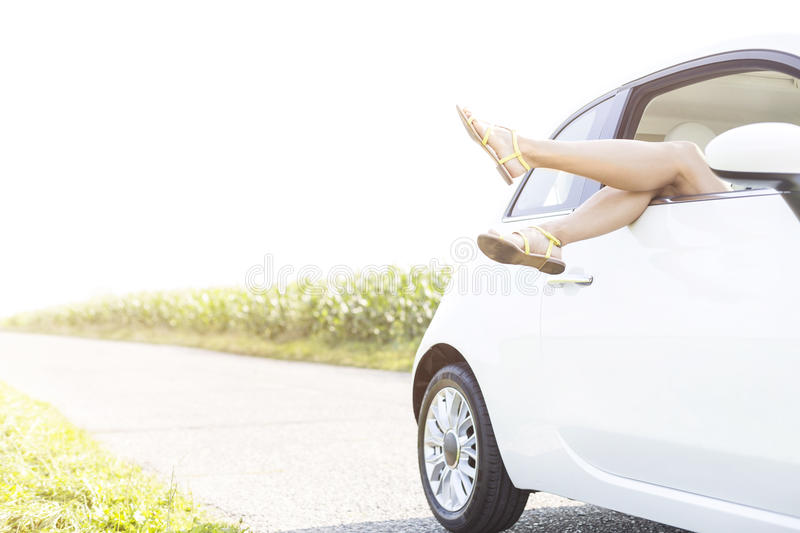 Low section of woman relaxing in car on country road against clear sky. Low section of women relaxing in car on country road against clear sky stock photos