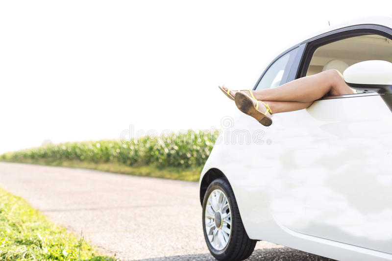 Low section of woman relaxing in car on country road. Low section of women relaxing in car on country road stock photo