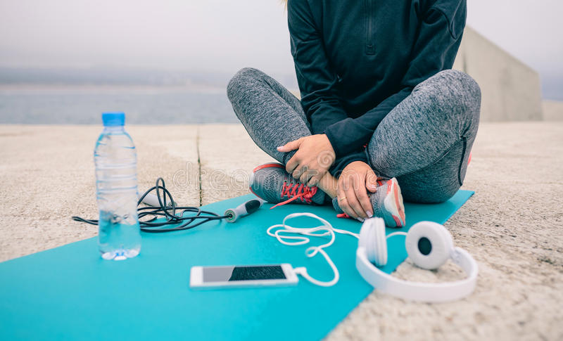 Low section of woman sitting with sport accessories. Low section of woman sitting on yoga mat with sport accessories stock photography