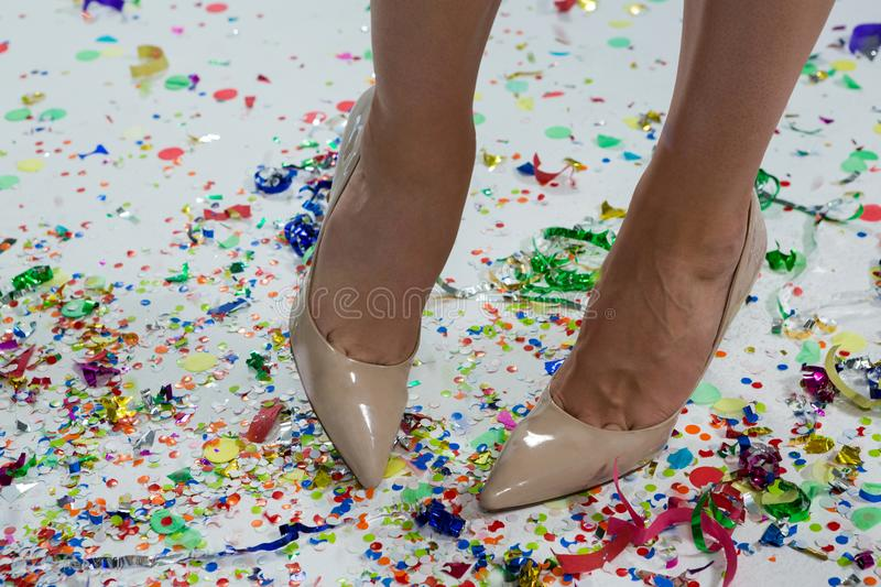 Woman standing wearing beige heels standing on the confetties royalty free stock photography