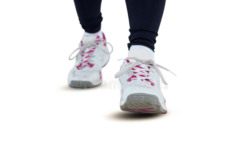 Low section of woman wearing shoes. Against white background stock images