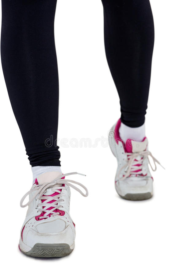 Low section of woman wearing sports shoes. Against white background stock photos