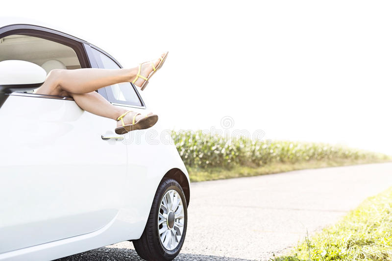 Low section of woman relaxing in car on country road against clear sky. Low section of women relaxing in car on country road against clear sky royalty free stock images