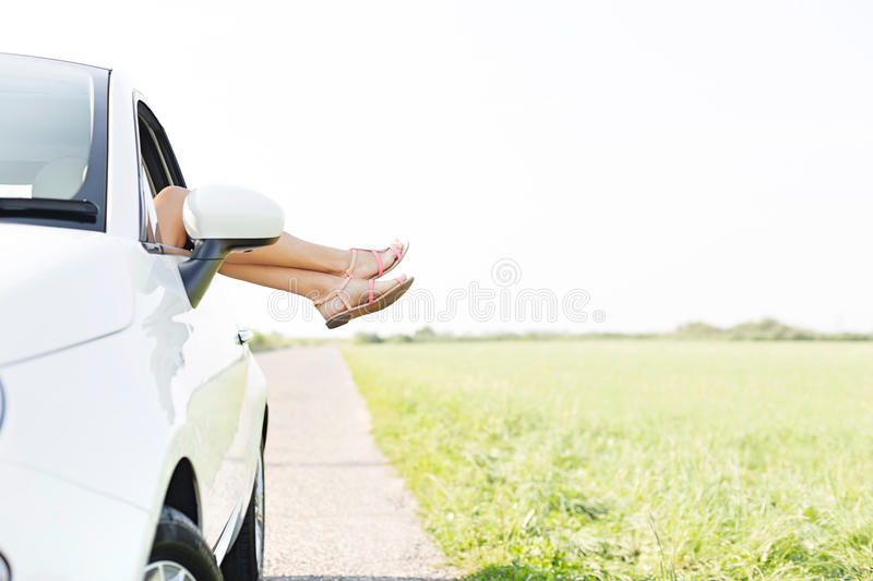 Low section of woman relaxing in car on country road. Low section of women relaxing in car on country road royalty free stock photos