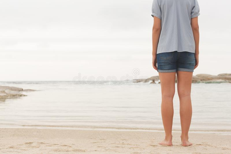 Young Caucasian woman standing at beach on sand stock images