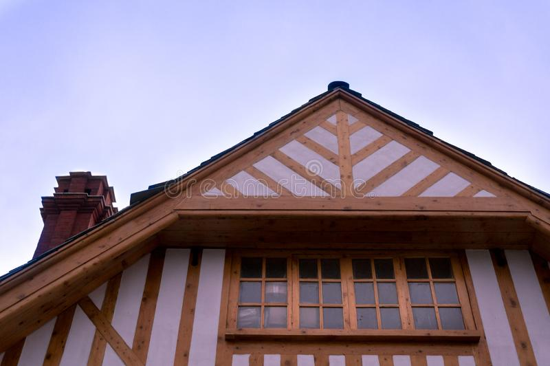 Low to high shot of a building with a sloping roof and wooden fr royalty free stock photo