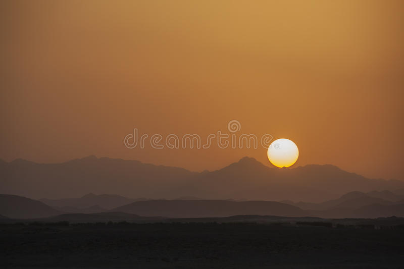 Low solar disk sets beyond hills royalty free stock image