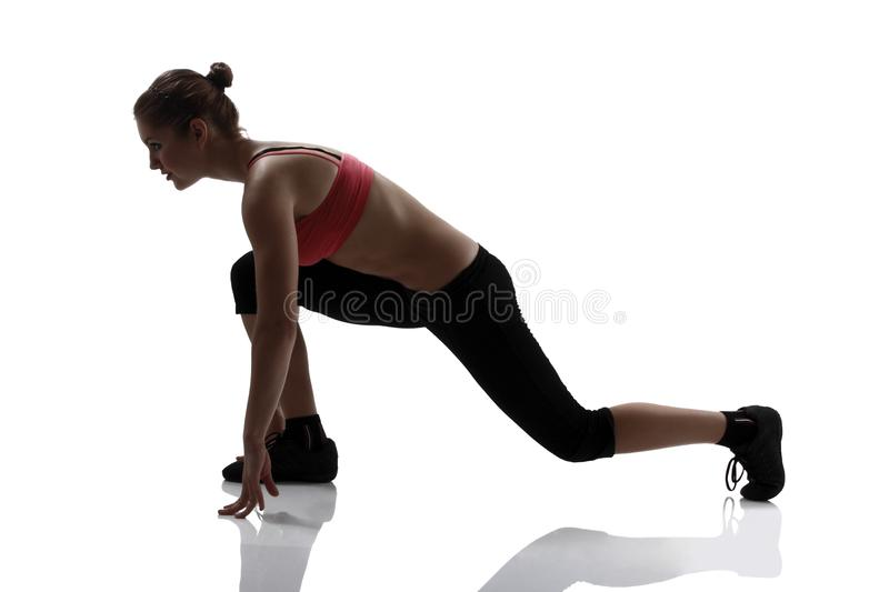 Low start, sport woman going to run, silhouette studio shot over. White background stock image