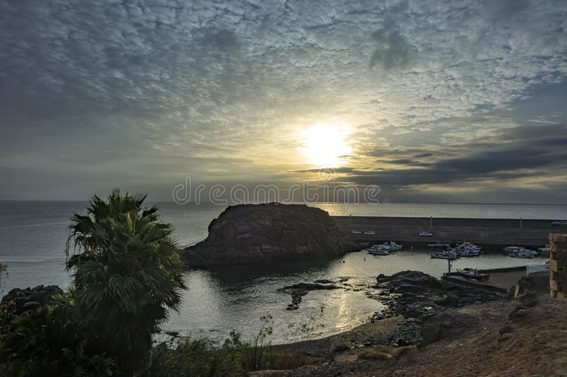 Low sun over the sea in El Cottillo Fuerteventura, Las Palmas,Canary Islands,Spain. Low sun over the sea, with an interesting sky over the harbour in El Cottillo royalty free stock image