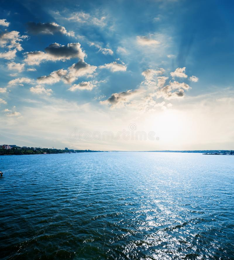 sunset in dramatic clouds over blue water in river stock images