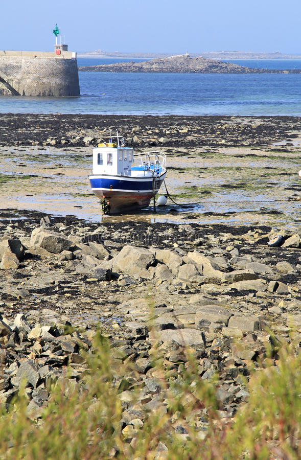 Low tide. Boat is stacked in low tide hours. Roscoff bay , Brittany , France stock photography