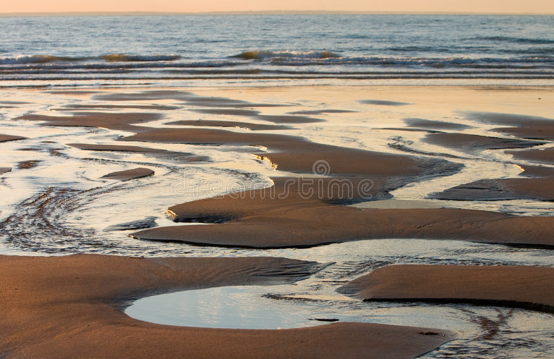Low tide. Water flowing out to sea at low tide royalty free stock photo