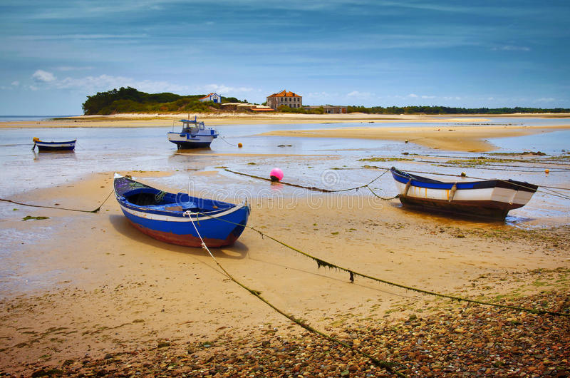 Low Tide. Four blue fishing boats in a beach with low tide royalty free stock image