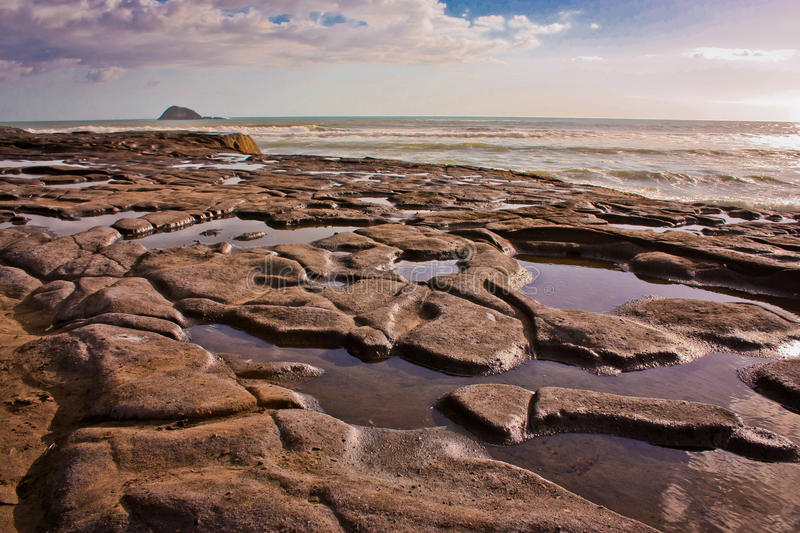 Low tide on Muriwai beach near Auckland, New Zealand. The low tide on Muriwai beach near Auckland in New Zealand royalty free stock images