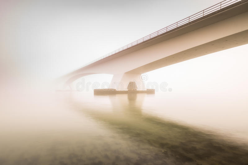 Low visibility due to heavy fog covering the Zeeland bridge, sun stock photos