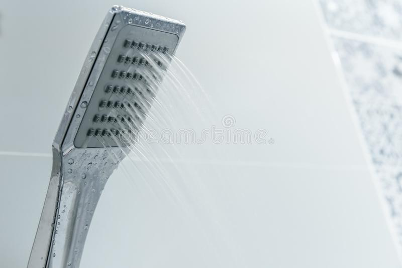 Low water pressure problem closeup at shower head. In white bathroom royalty free stock images