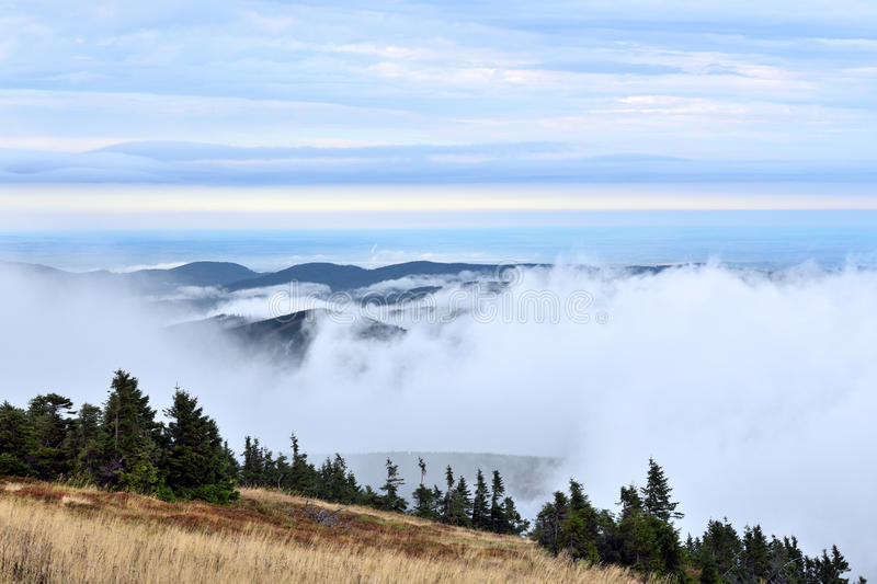 Low white clouds above distant forest hills landscape royalty free stock photo
