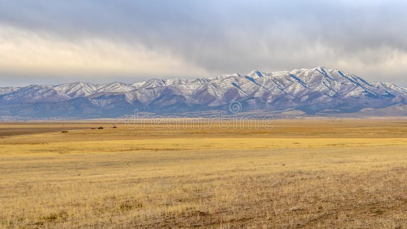 Lowe Peak beyond grassy terrain in Utah Valley. Spectacular cloudy sky over snow-capped Lowe Peak mountain and Utah Valley. A vast grassy terrain can be seen royalty free stock photography