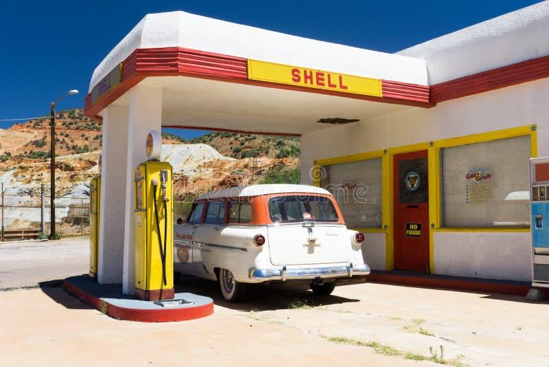 Lowell, AZ, de V.S./Juli 12 2016: oude brandstofpomp en klassieke auto bij een verlaten spookstadbenzinestation royalty-vrije stock foto's