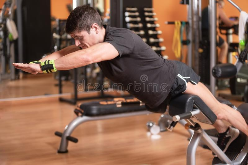 Lower back exercises for strengthening the muscles for spine health. Fitness man doing superman exercise workout with stock photography