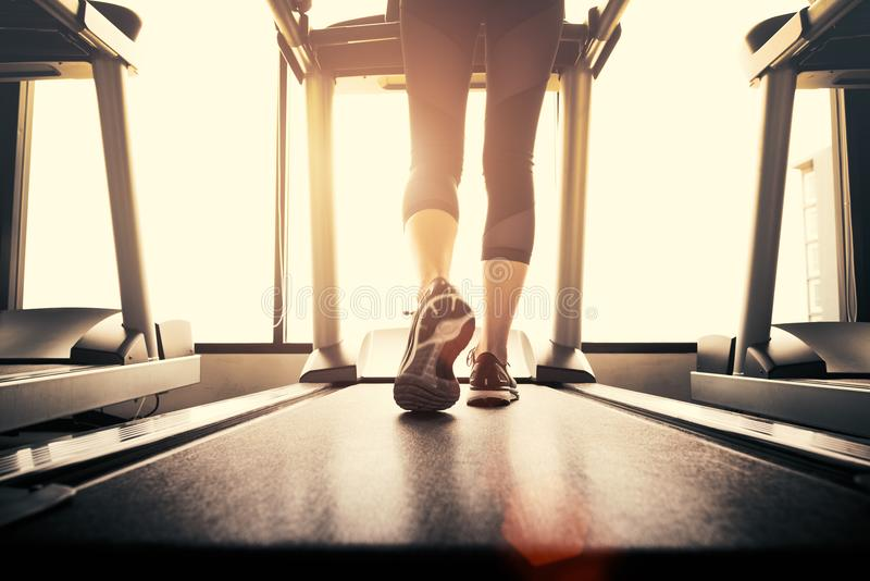 Lower body at legs part of Fitness girl running on running machine or treadmill in fitness gym with sun ray. Warm tone. Healthy stock photos