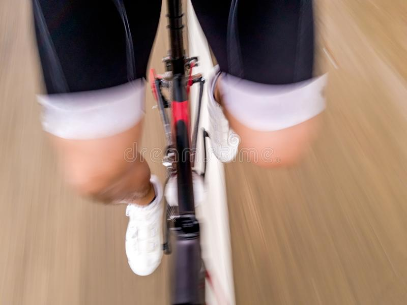 A Lower body part of a male cyclist in cyclist uniform riding road bike moving forward on the street with speed motion blur stock photo