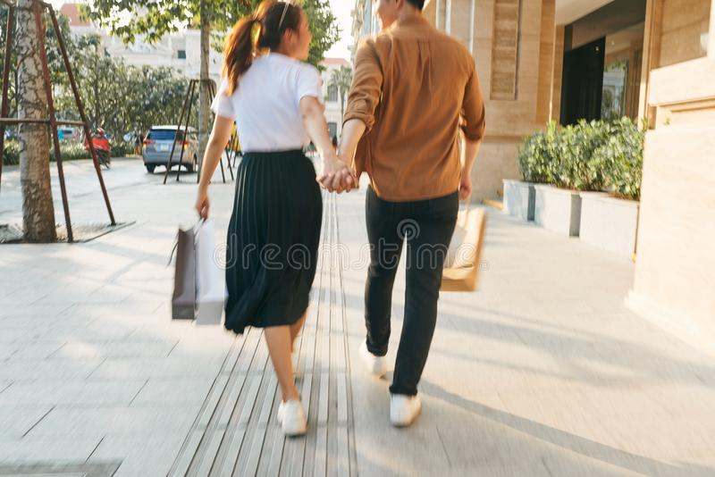 Lower body section of a young tourist couple walking by store windows and holding paper shopping bags in a destination city royalty free stock image