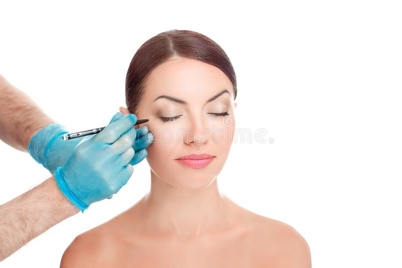 Doctor surgeon hand in gloves on patient face drawing cut line. Lower eyelid reduction wrinkles removal plastic surgery cosmetic operation concept Woman eyes royalty free stock images