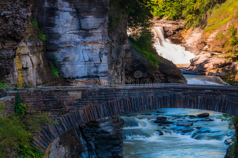 Lower Falls and a walking bridge across the gorge of the Genesee River, Letchworth State Park, New York. royalty free stock photography