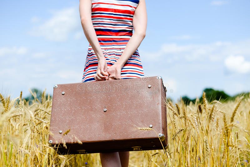 Lower half of woman holding old suitcase over stock photo