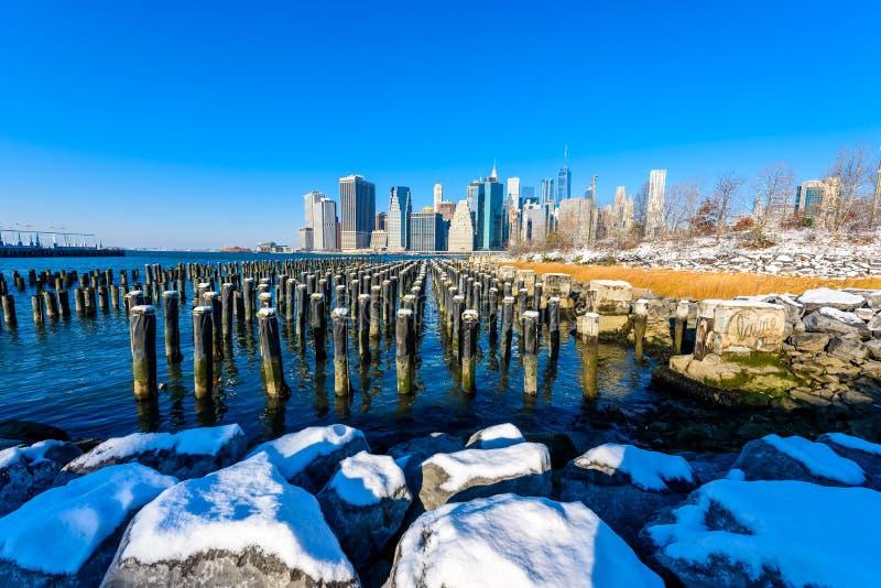 Lower Manhattan linia horyzontu panorama w śnieżnym zima czasie od mostu brooklyńskiego parka riverbank, Miasto Nowy Jork, usa obrazy royalty free