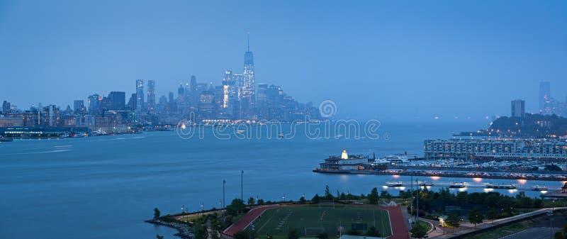 Lower Manhattan med tung nederbörd i afton och finansiella områdesskyskrapor och Weehawken som är ny - ärmlös tröjastrand New Yor arkivbild